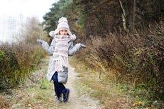 孩子女孩在秋天森林里 免版税图库摄影