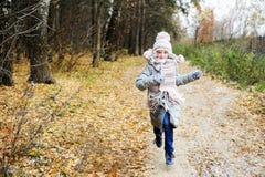孩子女孩在秋天森林里 库存图片