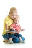 孩子女孩对她的兄弟的阅读书 免版税图库摄影