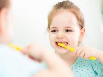 孩子女孩掠过的牙在卫生间里 库存照片