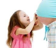 孩子女孩接触怀孕的母亲的腹部 库存图片