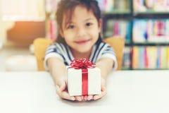 孩子女孩的礼物盒 有红色弓的白色箱子在女孩手上为给一件礼物 免版税图库摄影