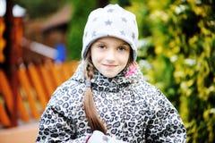 孩子女孩获得乐趣在有第一雪的庭院 免版税图库摄影