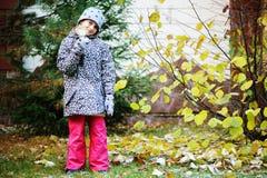 孩子女孩获得乐趣在有第一雪的庭院 库存图片