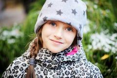 孩子女孩获得乐趣在有第一雪的庭院 库存照片
