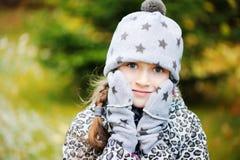 孩子女孩获得乐趣在有第一雪的庭院 免版税库存图片