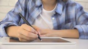 孩子学习在片剂的,写在学校课程的女孩,学会做家庭作业 免版税库存照片