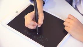 孩子学习在片剂的,写在学校课程的女孩,学会做家庭作业 库存照片