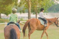 孩子学会在河附近骑马 免版税库存照片
