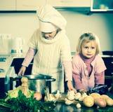 孩子学会如何准备食物 免版税库存照片