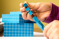 孩子学会算术、容量和容量 对学会模型使用一个三维立方体 免版税图库摄影