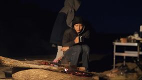 孩子孩子喝青少年的茶的微笑由火坐在夜营火 远足冒险野营的冒险野营的旅行 影视素材