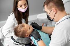 孩子安排他的牙出席由一位男性牙医在一相当女性和手套被协助的一个黑面具 库存照片