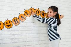 孩子帮助她的家庭挂上装饰 免版税库存照片