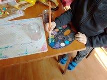 孩子弄湿在调色板的刷子与多彩多姿的油漆 儿童的创造性和绘的科学 创造性的活动  图库摄影