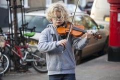 孩子弹小提琴在圣诞节市场 免版税库存图片