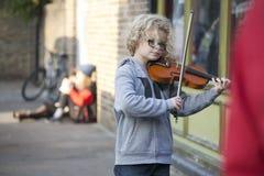 孩子弹小提琴在圣诞节市场 库存照片