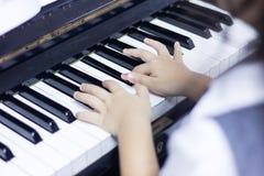 孩子弹钢琴 免版税库存照片