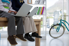 孩子当使用膝上型计算机的商业主管在办公室 库存照片