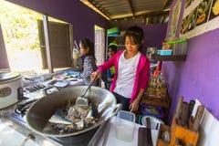 孩子得到食物在午餐时间在学校由项目柬埔寨人孩子关心帮助被剥夺的孩子 免版税图库摄影