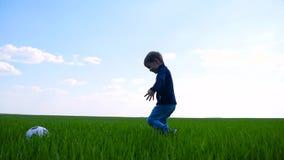 孩子愉快地踢足球并且横跨绿草的领域在慢动作的跑 股票视频