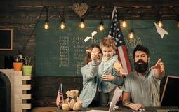 孩子戏剧 在书桌的美国家庭有做纸飞机的儿子的 Homeschooling概念 教儿子美国人的父母 免版税图库摄影