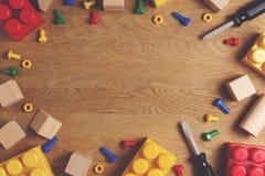 孩子戏弄与玩具工具、块和立方体的框架背景在木桌上 顶视图 平的位置 复制文本的空间 库存照片