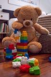 孩子戏弄与玩具熊和五颜六色的砖的背景 免版税库存照片