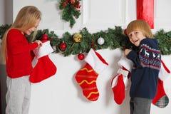 孩子打开圣诞节长袜 库存照片