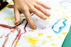 孩子执行在纸的一张图画与他的手指 库存图片