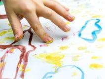孩子执行在纸的一张图画与他的手指 库存照片