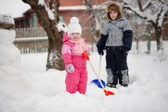 孩子扫清从雪的道路 库存照片