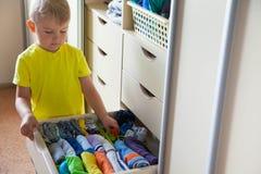 孩子投入他的衣裳  男孩拉T恤杉从里面 免版税库存照片