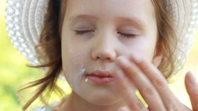 孩子抹上他的fase防晒霜晒斑 suncream 太阳保护奶油 特写镜头女婴 影视素材