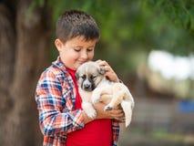 孩子拥抱一只小的小狗 孩子爱动物 免版税库存图片
