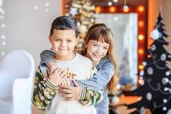 孩子拥抱和笑 背景兄弟查出的姐妹白色 概念愉快的基督 免版税库存照片