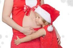 孩子拥抱孕妇在圣诞节,雪花的腹部 库存图片