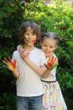 孩子拥抱,他们的面孔和手在油漆 免版税库存照片
