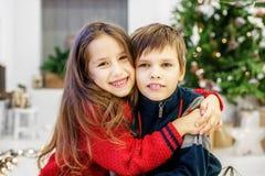 孩子拥抱 男孩和女孩 愉快的圣诞节和 免版税库存照片