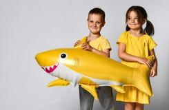 孩子拿着一个气球以一条黄色鲨鱼鱼的形式,庆祝假日,广泛微笑,在轻的背景的立场, 库存照片
