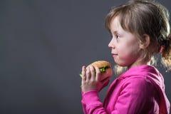 孩子拿着一个汉堡包,在灰色背景的一张照片与拷贝空间 免版税库存图片