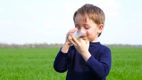 孩子拿着一个绿色苹果和一杯苹果汁 在自然背景和笑的男孩饮用的汁液 股票录像