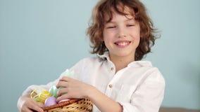 孩子拿着一只复活节兔子和一套装饰复活节彩蛋 男孩快乐地笑 慢的行动 股票录像