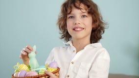 孩子拿着一只复活节兔子和一套装饰复活节彩蛋 男孩快乐地笑 慢的行动 影视素材