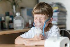 孩子拿着一台面具蒸气吸入器 库存图片