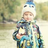 孩子拿着从秋天叶子,概念, instagram的一条小船 库存图片