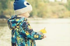 孩子拿着从秋天叶子,概念, instagram的一条小船 免版税图库摄影