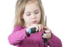 孩子拿着剪刀和一把螺丝刀 免版税库存照片