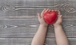孩子拿着在树纹理的背景的红色心脏 免版税库存图片