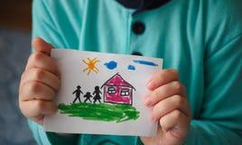 孩子拿着有家庭的一个拉长的房子 库存图片